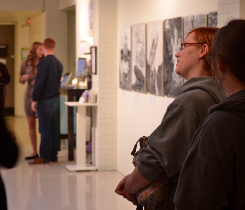 Campus community members observe art at the opening of the 2016 senior art and design capstone exhibition in Hermann. Photo by Matt Peters.