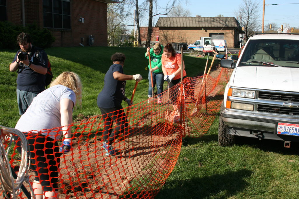 Student volunteers work to create a new sidewalk on Butler Street as a part of Community Service Day 2016.