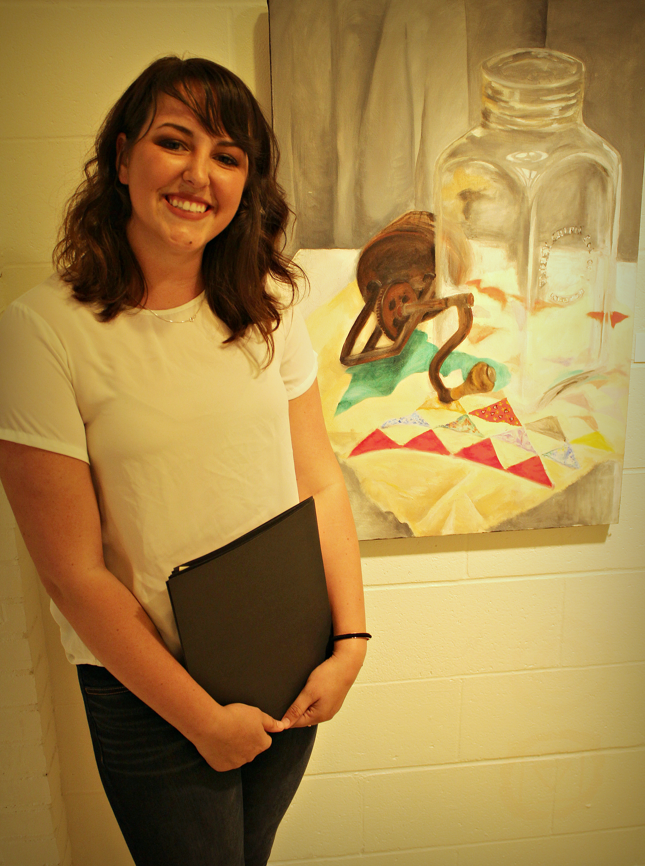 """Senior, Laken Lyon stands in front of her painting """"Butter Churn & Quilt."""" Photo by Matt Peters."""